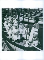 Old ladies  wearing sailor uniforms on a rowing boat.