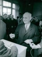 Gaston Defferre standing in front of a ballot box, 1965.