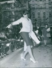 Beautiful woman dancing in street, other women standing behind looking at her.