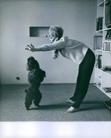 Vivi Bach playing with her pet dog.