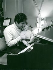 Sacha Distel playing piano with his son, 1967.