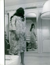 Dalida in her room fitting a dress.
