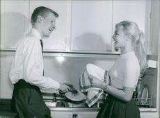 Service man and woman standing and talking in the Kitchen.