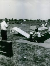 Woman posing with children beside coffin.