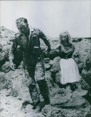 Stewart Granger in the soldier uniform, holding hand of a woman and walking.