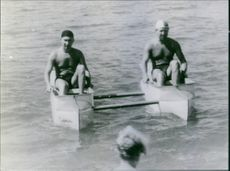 Two men paddling in boats.