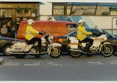 Motorcycle policemen with a new model and older Harley Davidson