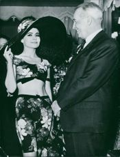 Maurice Auguste Chevalier standing with a woman and talking 1963