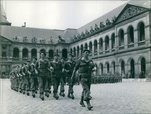 French army marching in an open ground during a ceremony in Les Invalides.