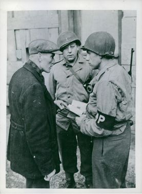 U.S. soldiers question German civilian and checking his identity