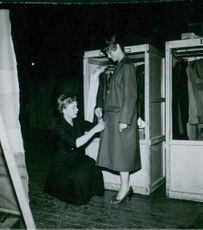 A woman being dressed by another woman in 1955.