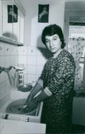 A woman doing the dishes, 1970.