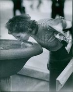 Busy woman shopper has hand full of bundles drinking water to a fountain.