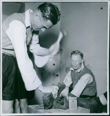 A shoemaker repairing shoes, while another man looking. 1939