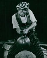 In his take-off of the strong man act, Popov the clown makes fearful grimaces as he struggles to lift a fake weight.