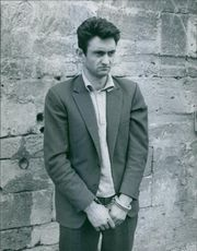 Man wearing handcuffs and looking at someone. 1964