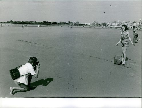 Minou Drouet standing on the beach shore, striking a pose, eyes closed, with a man taking the picture, 1962.