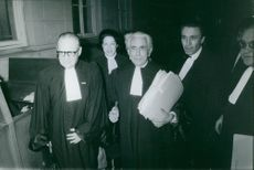 Lawyers standing together and holding papers. 1970