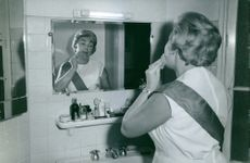 A LADY IN WASHROOM & LOOKING AT MIRROR