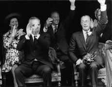 Prince Bernhard of the Netherlands waving along with other people, while holding a camera during an event.