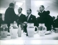 Ferhat Abbas is standing with other politicians. 1959