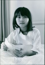 A girl sitting on bed, looking towards the camera and smiling.