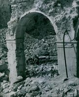 Through one of the few remaining arches of the cloisters of the Monastery, German P.O.W. stripped to the waist, labor in the hot sun removing masonry.People taking out the things from the debris of a ruin after the war.