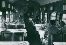 Soldiers eating at a lounge car of a train.