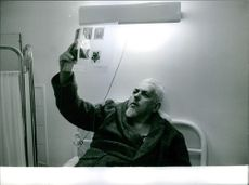 A man lying on a hospital bed looking at a transparent sheet with pictures on it. December 14, 1964.