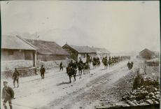 Soldier riding their horses marched on a dirt road on a residential area, 1904.