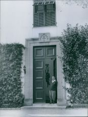 W. Somerset Maugham standing in the entrance of a house.