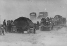 Military trucks with soldiers moving on the ground.