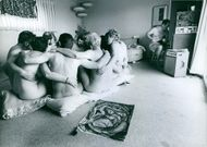 A group of naked people in one big group, with their arms wrapped around each other.