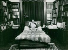 Maurice Chevalier sitting on bed.