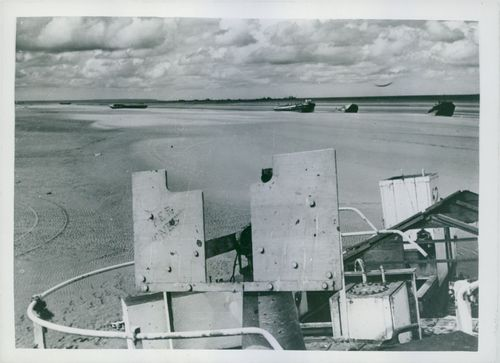 The re-birth of France: Landing craft and beach equipment lie along the rippled sands  of Utah beach, once a scene of battle.