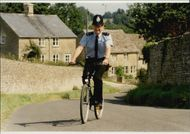 Policeman on a bike in the countryside