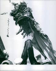Man standing, holding a huge monster mask and looking at something.
