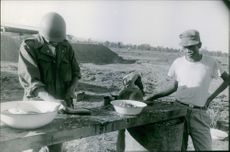 Laos (Laotian Civil War 1953–75) A photo of a Military personnel in Laos cleaning a fish; war in Laos  they still find to make food.