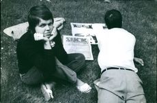 Two people lying on the grassy ground, reading magazines, 1970.