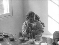 A young girl, carrying a small child on his back, is sipping from a cup.