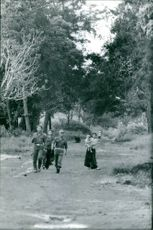 Uniformed men and two women carrying children are walking somewhere in Indochina.