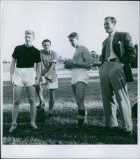 footballer standing on the ground with coach during training.  1945