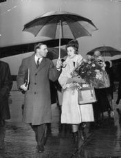 Princess Alexandra holding  flowers, with a man holding an umbrella.