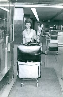 Juliana smiles as she holds her trophy and pushed a cart holding her baggages at the airport.