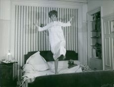 France Anglade skipping rope on bed and looking towards the camera.