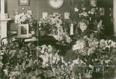 Cecilia Milow surrounded with flowers.