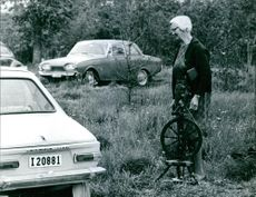 Auktion pa Gotland, borjan pa 70-talet (Auction on Gotland, the beginning of the 70s) A woman standing in front of cars park on the woods of Gotland for auction.