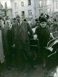 Charles De Gaulle is holding the hand of his spouse.