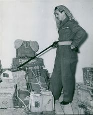 A soldier from Jordan, pointing a stick to show boxes of explosives that are in the room. Jordan.