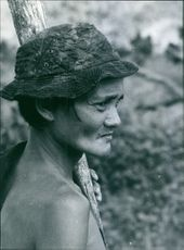 Vintage photo of a Malaysian Women wearing hat and holding a wooden stick.